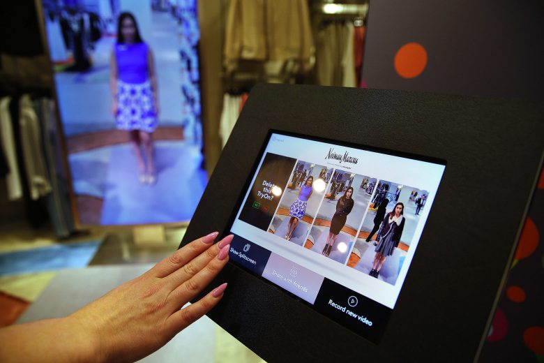 In this photo taken Wednesday, April 15, 2015, sales manager Alysa Stefani uses a touchscreen display to make selections while demonstrating the Memory Mirror at the Neiman Marcus store in San Francisco's Union Square. The mirror is outfitted with sensors, setting off motion-triggered changes of clothing. The mirror also doubles as a video camera, capturing a 360 degree view of what an outfit looks like and making side-by-side comparisons. (AP Photo/Eric Risberg)