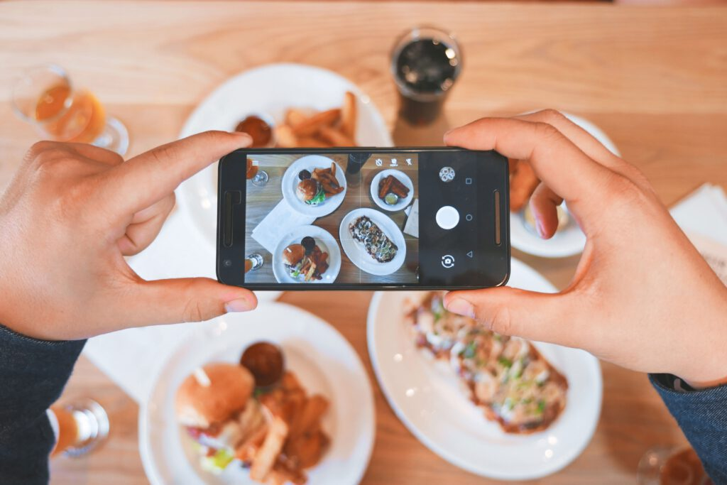 person taking a picture of food on their phone